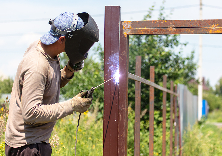 A worker welds metal for a fence